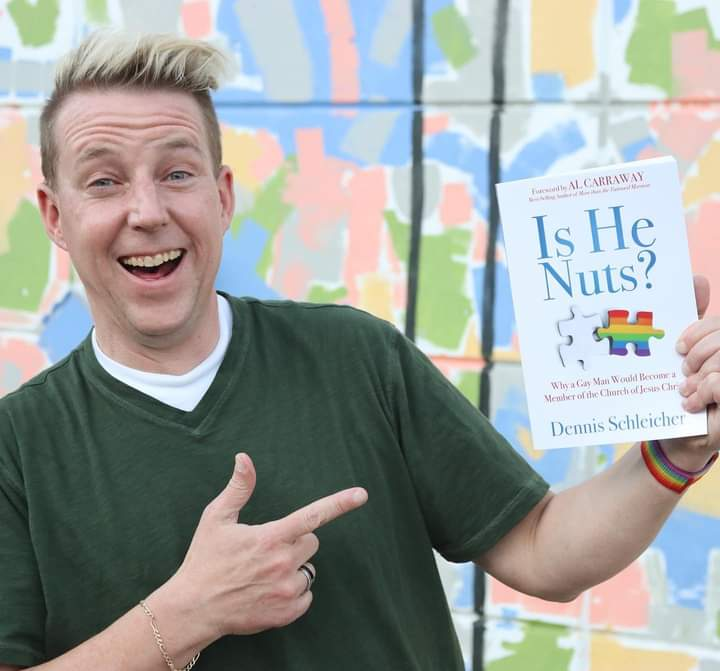 A blonde man with short hair pointing at the book (out of frame) with his other hand and smiling in front of a pastel wall